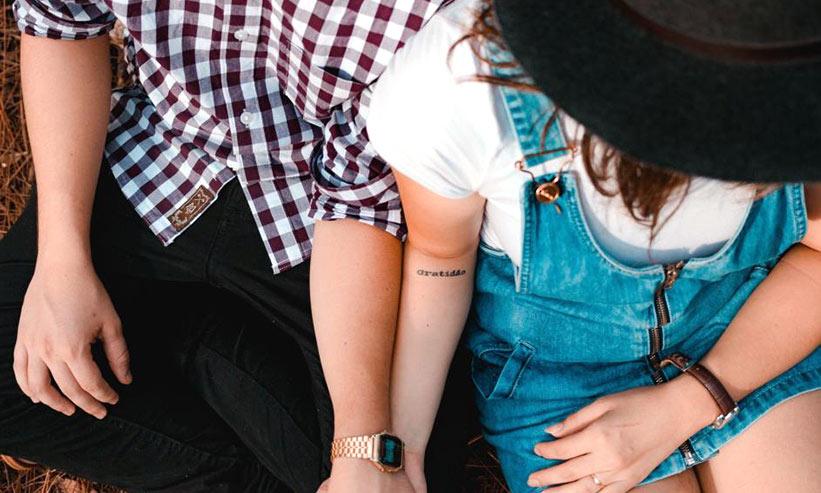 手を繋ぎながら座っているカップル