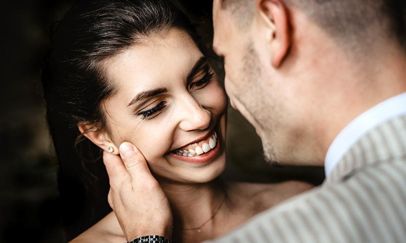 男性に頬を触られにっこりと微笑む女性