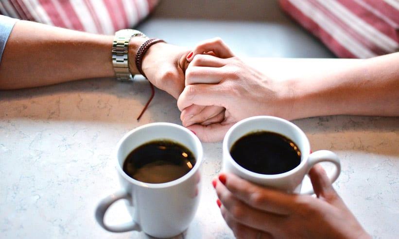 カフェのテーブルで手を握り合うカップル