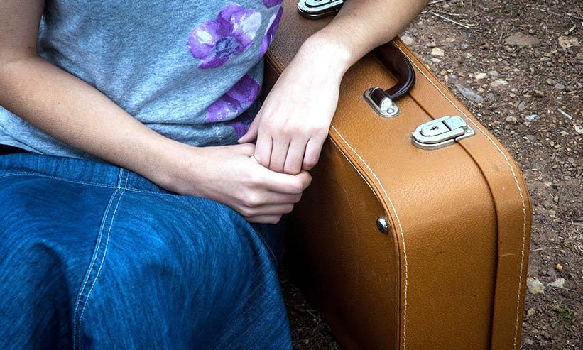 キャリーケースに肘をついて座っている男性