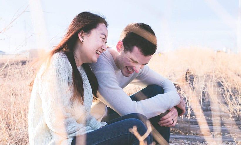 草原で座りながら笑い話をしているカップル