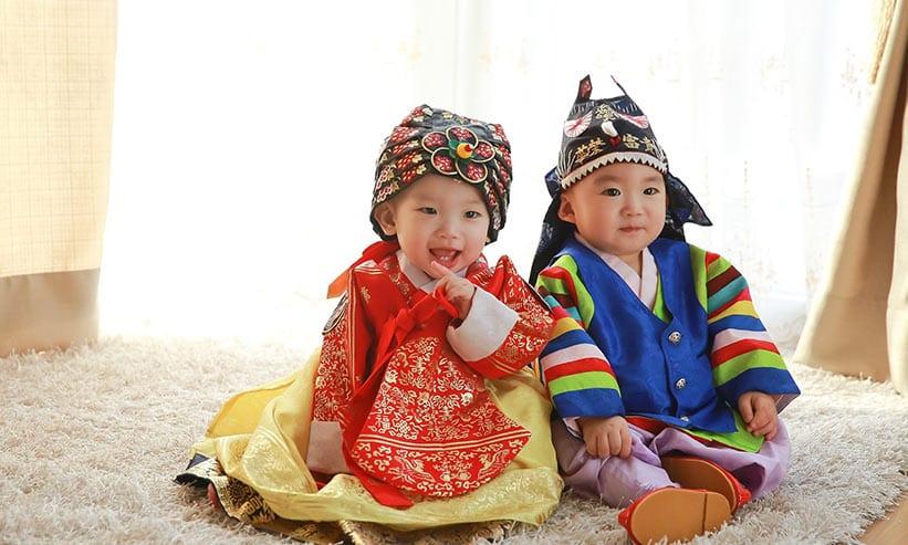 民族衣装を来て座っている2人の子供
