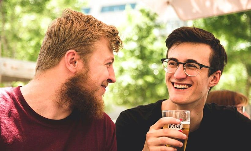 笑いながらお酒を飲んでいる男性2人