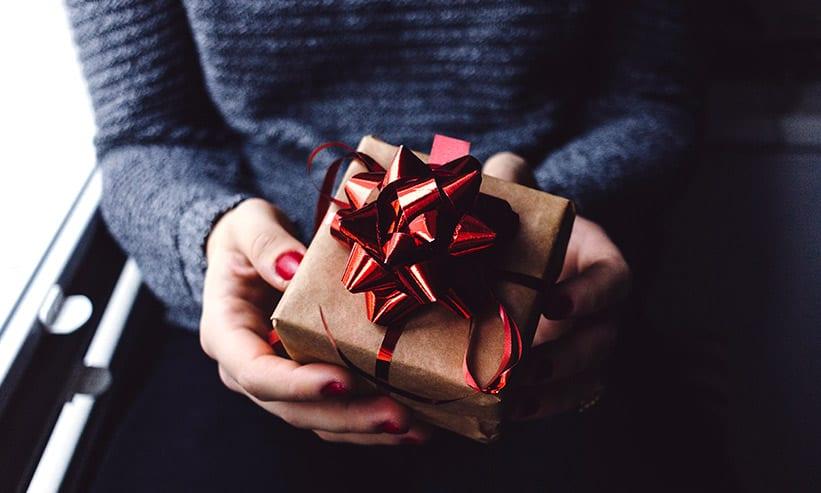 リボンの付いた小さなプレゼントを持っている女性