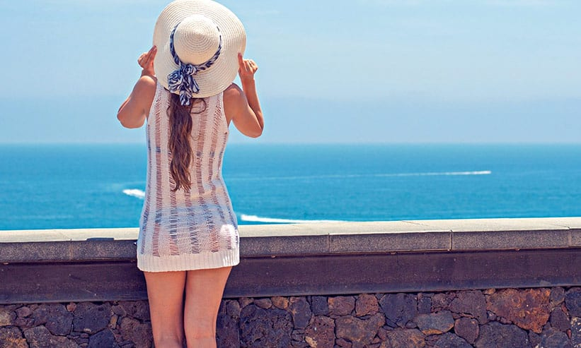 麦わら帽子を押さえながら海を見ている女性の後ろ姿