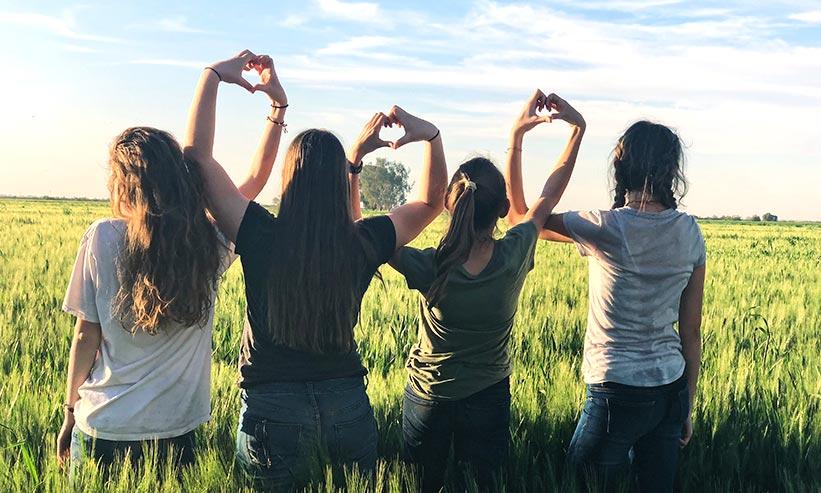 横に一列で手を上げハートマークを作る4人の女性