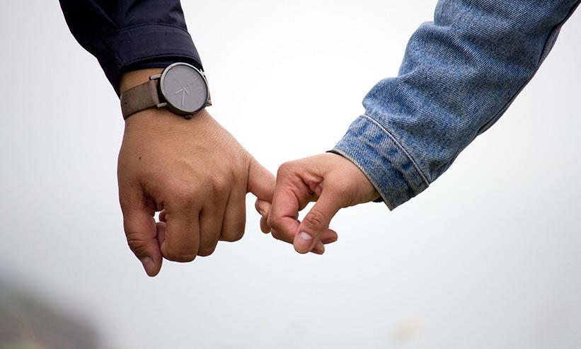 男性の小指を掴む女性