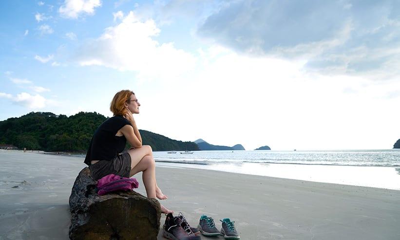 浜辺で流木に座り海を眺める女性
