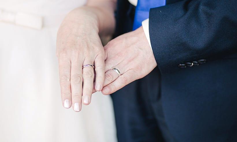 指輪を見せるように左手を重ね合う夫婦