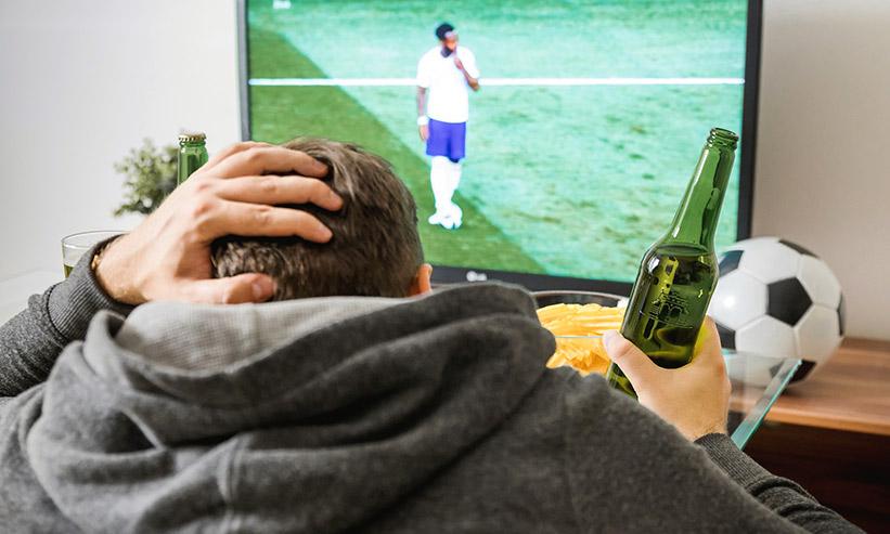 テレビでサッカーを見る男性