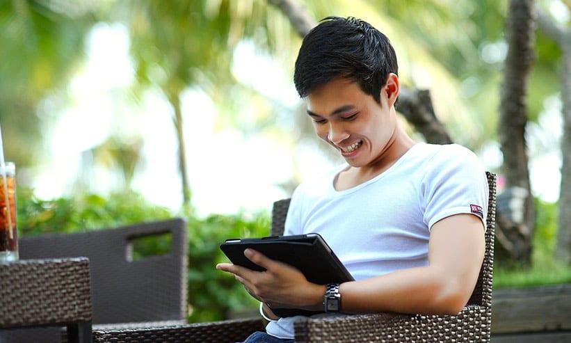 笑顔でタブレットを操作する男性