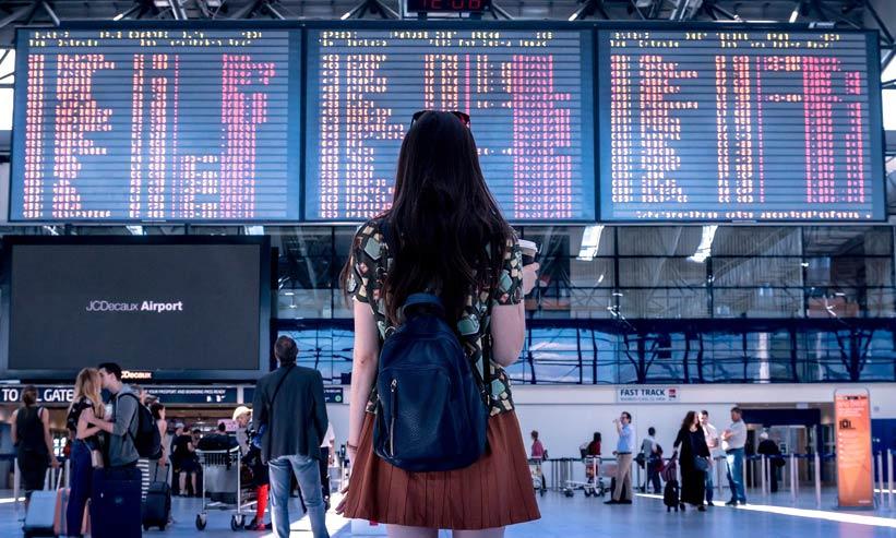 空港の電光掲示板を見ている女性