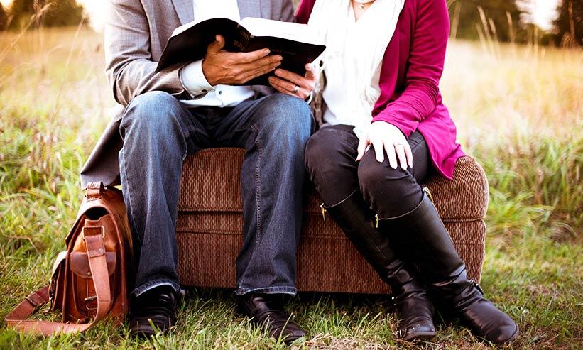 外で本を読むカップル