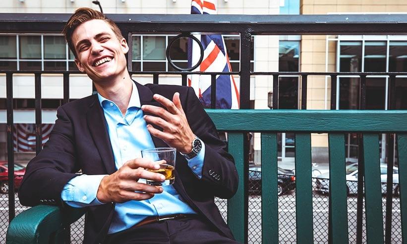 ベンチに座り楽しそうにお酒を飲む男性