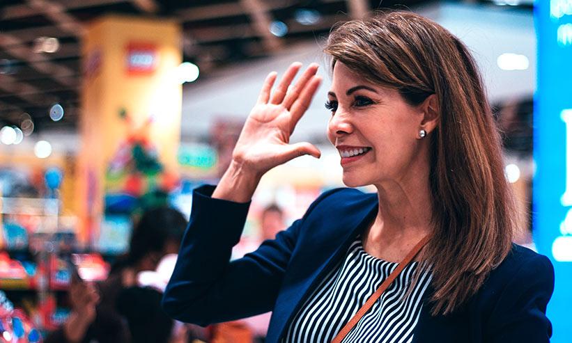 手をあげて微笑んでいる女性