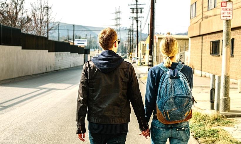 手を繋いで歩くカップルの後ろ姿