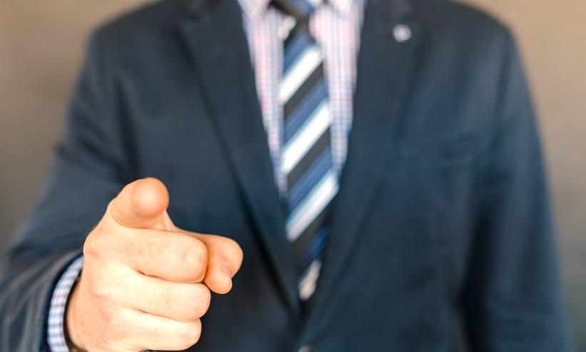 指差ししているスーツの男性