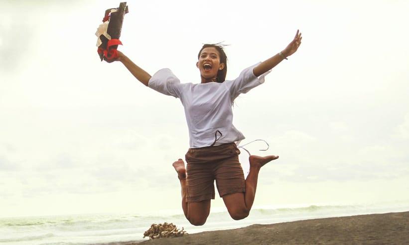 砂浜で手を広げてジャンプする女性