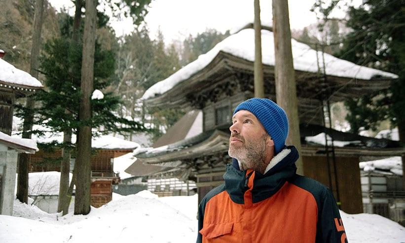 雪が積もった神社を眺める外国人
