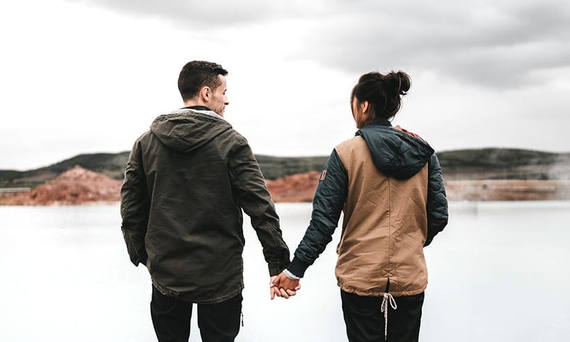 手を繋いで見つめ合うカップルの後ろ姿
