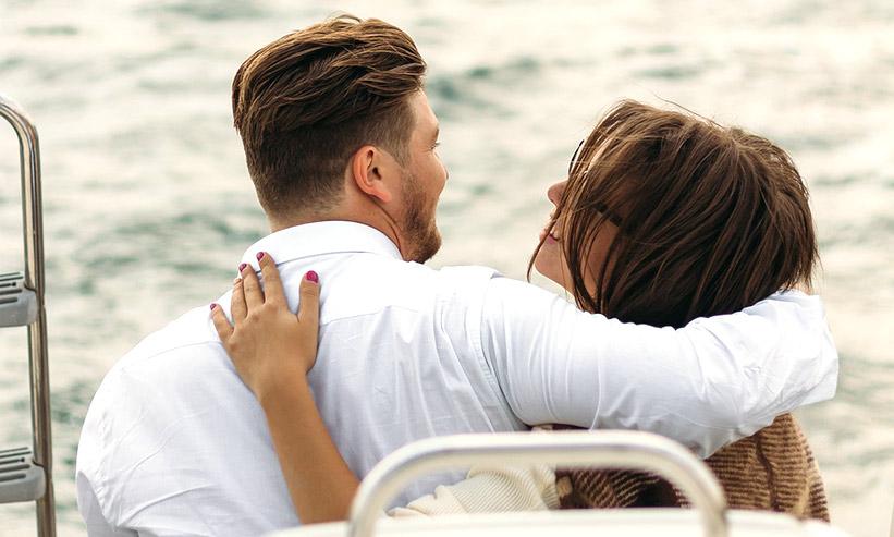 肩を組むカップルの後ろ姿