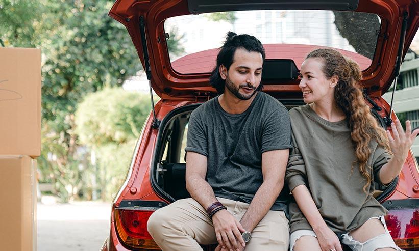 車のトランクに座り話しているカップル
