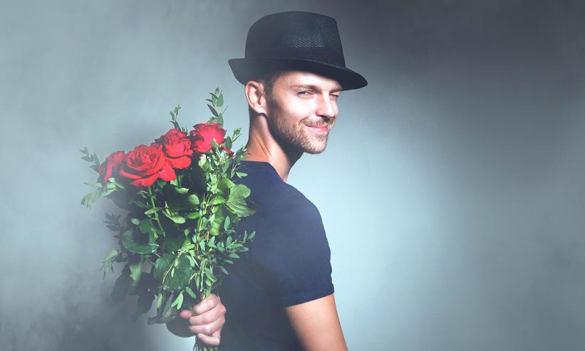 薔薇の花束を背中に隠す男性