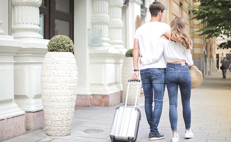 キャリーケースを押し旅行に出かけるカップル