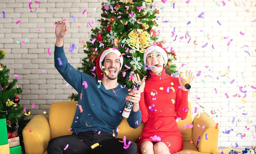 クリスマスツリーの前で盛り上がるカップル