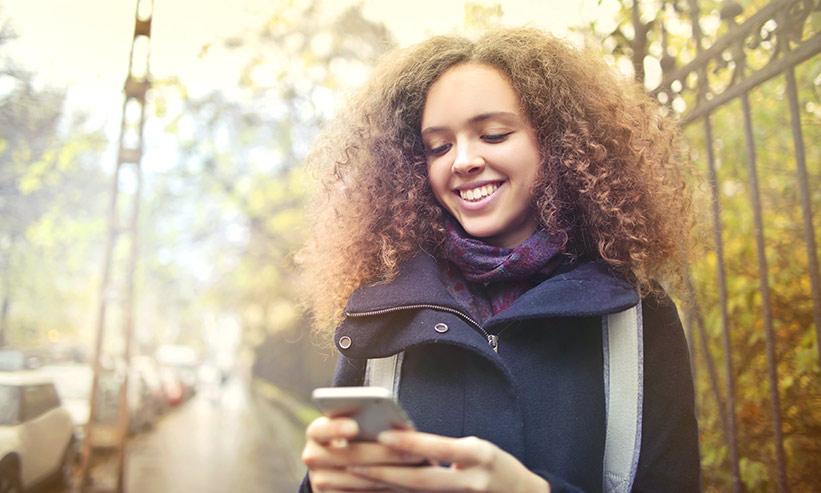 微笑みながらスマートフォンを見つめる女性