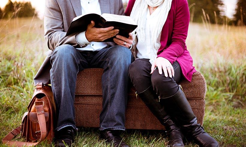 椅子に座り本を読んでいるカップル