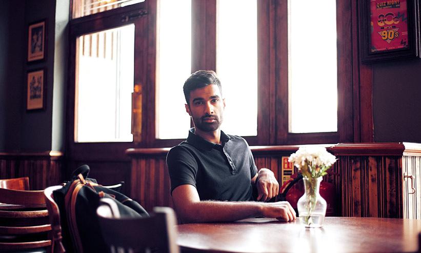 レストランのテーブル席に一人で座っている男性