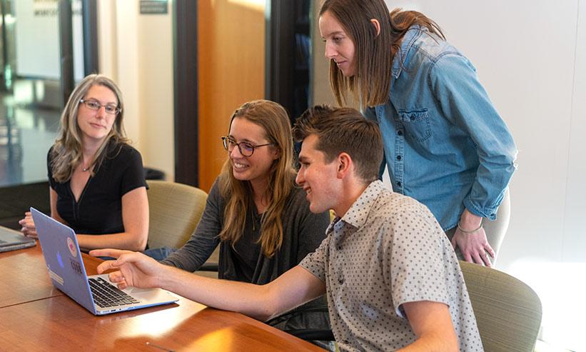 パソコンを見ながら話をしている4人の男女