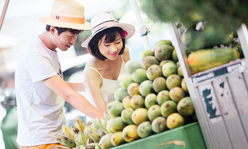 お店でフルーツを買っているカップル