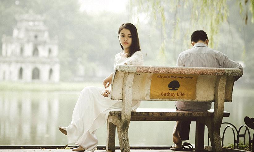 男性とベンチに座りそっぽを向いている女性