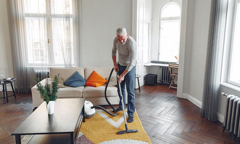 リビングを掃除する男性