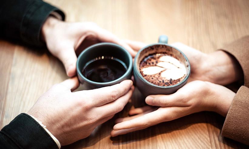 コーヒーを一緒に飲んでいるカップルの手元