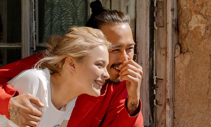 窓際で笑いながら外を見つめるカップル