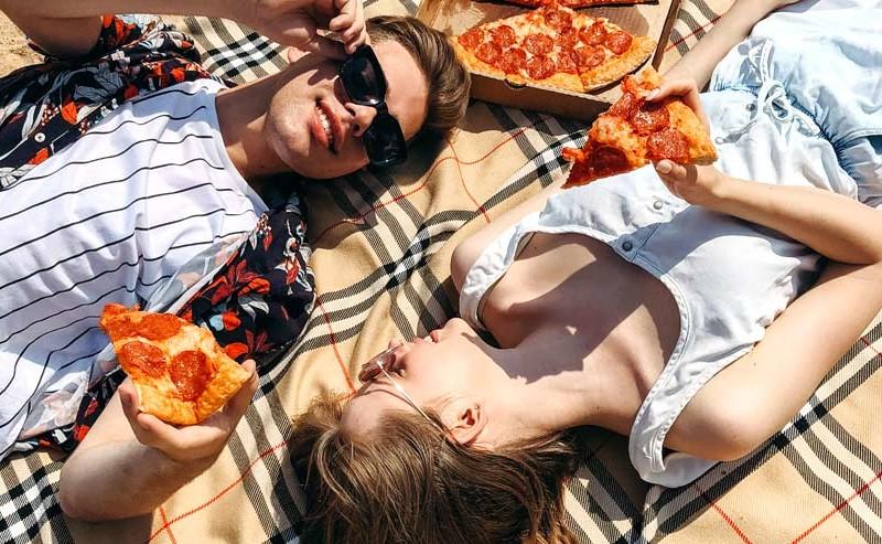 寝転んでピザを食べるカップル