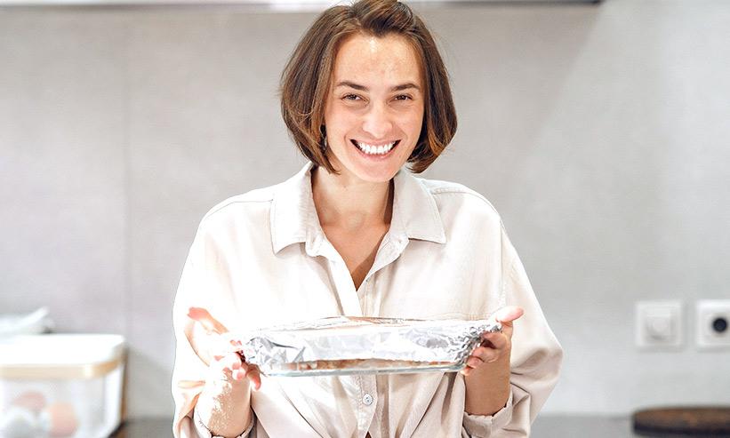 満面の笑みで料理を持つ女性