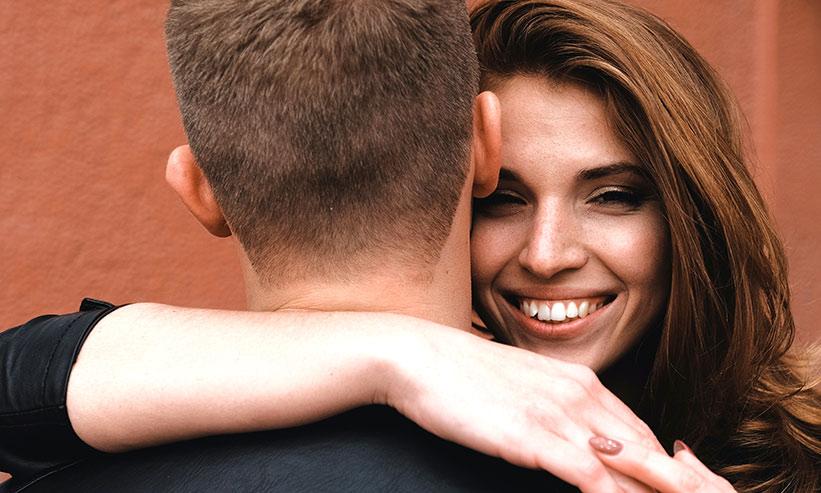 笑いながら男性を抱きしめる女性