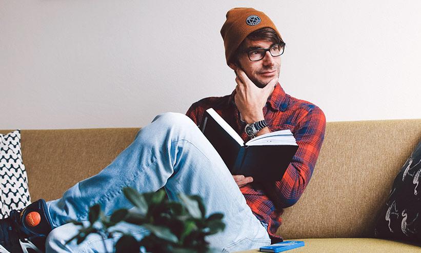 ソファに座り本を読む男性
