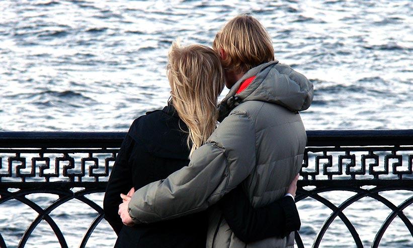 お互いの腰に手を回し海を眺めるカップル