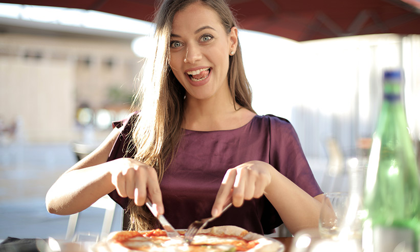 笑いながらピザを食べる女性