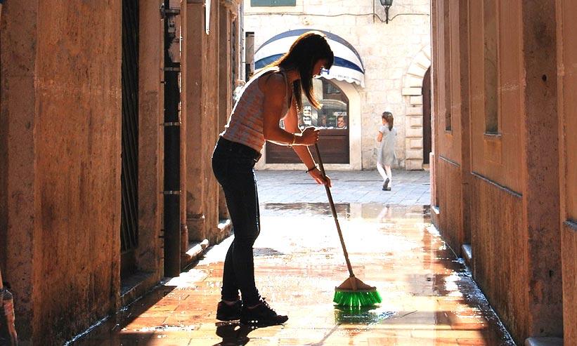 路地を掃除中の女性