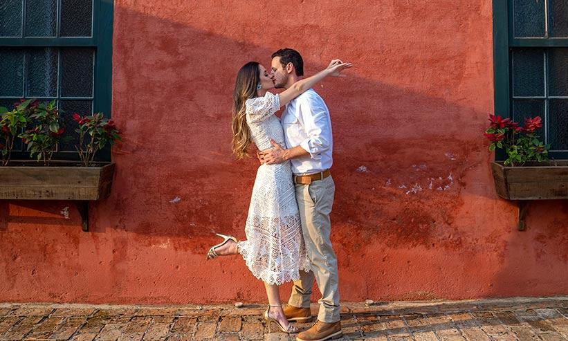 赤い家の前でキスをするカップル