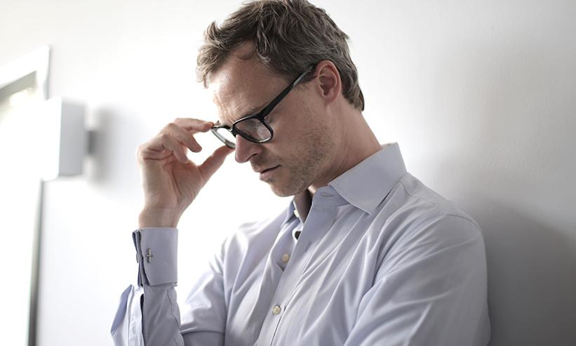 メガネに手をあて考え事をしている男性
