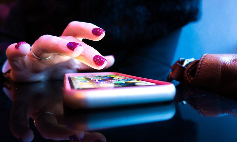 スマートフォンをタップしようとしている女性の手