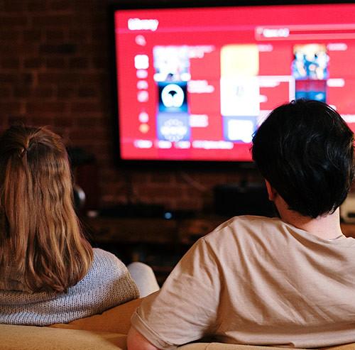 テレビを見ているカップルの後ろ姿
