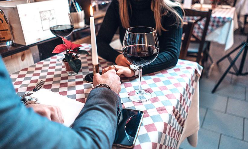 レストランで手を握り座っているカップル